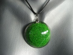 Large cabochon pendant, green miniprees, in resin