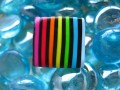 Small pop ring, multicolored stripes, on a black background, in Fimo
