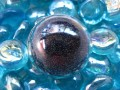 Dome ring, mobile black microbeads, in a plexi half-sphere