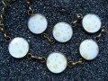 Small cabochons bracelet, golden peas on a white background