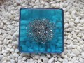 Very large square ring, silver microbeads, on a blue resin background