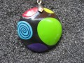 Pop pendant, multicolored patterns, on a black Fimo background