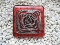 Very large square ring, silver graphic print, on a red resin background