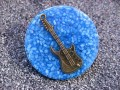 Very large ring, bronze guitar, on a blue resin background