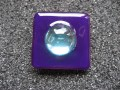 Large square ring, turquoise pearl, on plum resin background