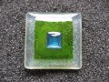 Very large square ring, turquoise pearl, on a green and white pearly resin background