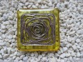 Very large square ring, silver graphic print, on a yellow resin background