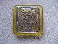 Large square ring, silver graphic print, on yellow resin background