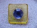 Large square ring, blue pearl, on yellow resin background