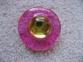 Large graphic ring, yellow pearl, on resin fuchsia background