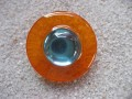 Big graphic ring, orange pearl, on a white resin background
