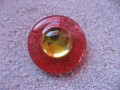Big graphic ring, yellow pearl, on a red resin background