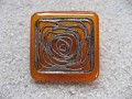 Large square ring, silver graphic print, on orange resin background