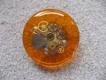 Big ring, the cogs of time, on orange resin background