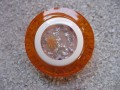 Large graphic ring, transparent white cabochon with flowers, on orange resin background