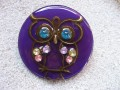 Very large graphic brooch, bronze owl, on purple resin background