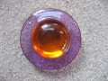 Very large graphic ring, large orange pearl, on a purple resin background