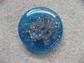 Very large adjustable graphic ring, silver microbeads, on blue broken resin glass background