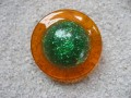 Large graphic ring, green glittered cabochon, on orange resin background