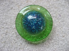 Large graphic ring, glittery blue cabochon, on green resin background