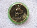 Large ring, bronze skull, on a green resin background