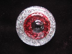 Large ring, black pearl, on a red glittery and silvery resin background