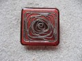 Large square ring, silver graphic print, on a red resin background