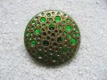 Large graphic ring, perforated bronze stamp, on a green resin background