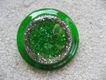 Very large graphic ring, green glitter, on a silver and green resin background