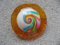 Very large ring, multicolored spiral on white fimo background, on orange resin background