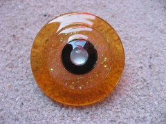 Very large adjustable ring, black pearl, on a pearly white and orange resin background