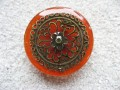 Large ring, Bronze Mandala Star, on an orange-red resin background
