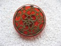 Large graphic ring, bronze stars, on a red resin background