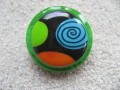 Large ring, multicolored cabochon on a black fimo background, on a green resin background